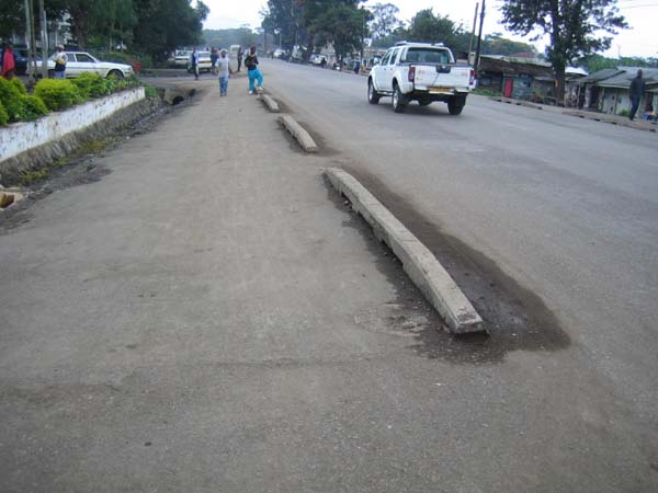 This footway adjacent to a road in Tanzania is protected by curb pieces which separate motor traffic from pedestrians and bicycles. Such basic safety measures are needed to prevent pedestrian injuries along roadways in many countries.