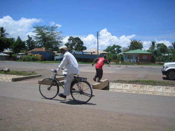 Even better, pedestrian and non-motorized traffic can be kept safely removed from motorized traffic by accessible sidewalks separated from the roadway, in this case by a well-designed drainage system along a main road in Tanzania. Speed bumps are used to slow traffic at crosswalks.