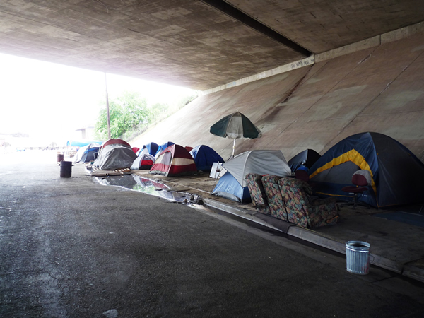 A Homeless Encampment situated in Fresno, California, USA. Encampments under highway overpasses are common in the US, not only for the structural protection from the elements, but because highway property is not part of city jurisdictions and can avoid the frequent evictions of police faced by those on other public property. Photo by Christopher Herring.