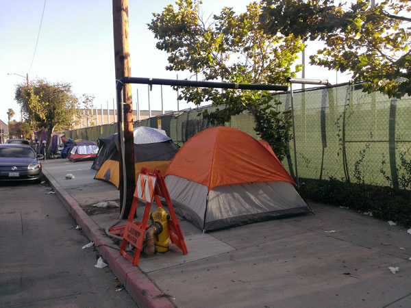 Tents:  A temporary homeless encampment on the sidewalk bordering the campus of the Los Angeles City College in Los Angeles, U.S.A.  The City College is a community institution that provides a stepping stone to full-degree programs at other colleges and universities.  Inside the fence, 20,000 mainly low- and lower-income students pursue their dreams of a better life .  Outside the fence, the main preoccupation is to find a place to sleep.  Photograph by Benjamin Clavan, 2015.