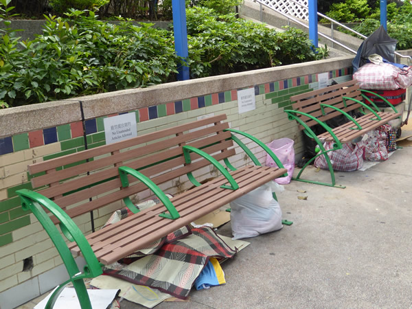 "Park benches serve as ""home"" for those without shelter, each of whom neatly stack their belongings beneath their chosen spot in Hong Kong.  Photo by Benjamin Clavan, 2015."